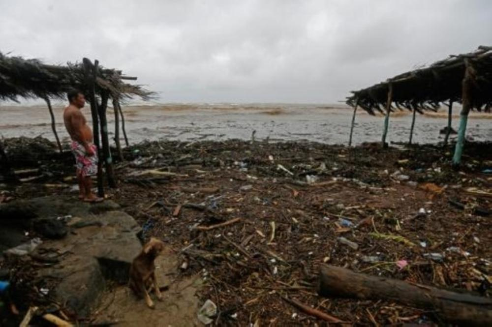 رجل ينظر للأمواج المرتفعة أثناء هطول أمطار غزيرة جراء مرور العاصفة الاستوائية
