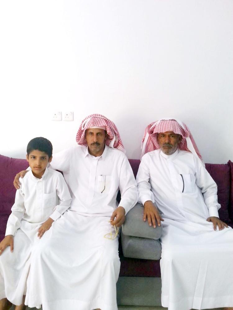 والد الشهيد محتضنا ابنه الأصغر مشعل وبجواره عم الشهيد