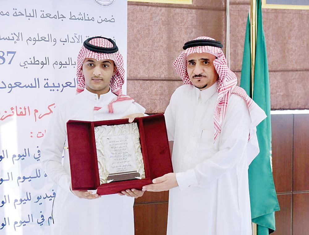 مدير جامعة الباحة يكرم أحد المشاركين.