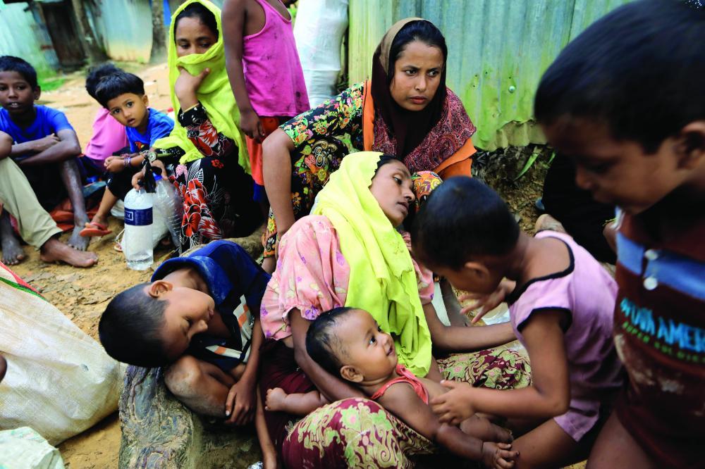 روهينغيون يعبرون الحدود إلى بنغلاديش بعد فرارهم من بورما أمس.   (رويترز)