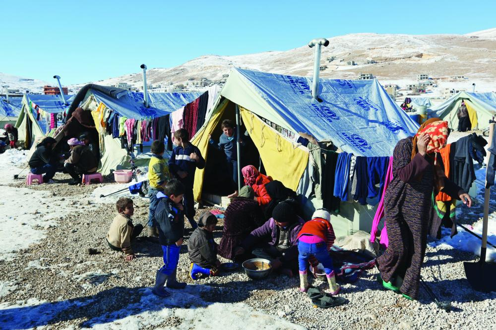 Syrian refugees eat their lunch outside their tents at a refugee camp in the eastern Lebanese border town of Arsal, Lebanon, Sunday, Dec. 15, 2013. Tens of thousands of impoverished Syrian refugees living in tents, shacks and unfinished buildings throughout Lebanon face a miserable winter as aid organizations scramble to meet their needs, constantly overwhelmed by ever-more Syrians fleeing their country's war. Charities have already distributed blankets, mattresses, kerosene heaters, winter clothes and coupons for fuel ahead of the region's unprecedented storm this week that blanketed parts of Lebanon, the Palestinian Territories, Turkey, Israel and even Egypt's deserts with snow, amid icy and rainy winds. (AP Photo/Bilal Hussein)