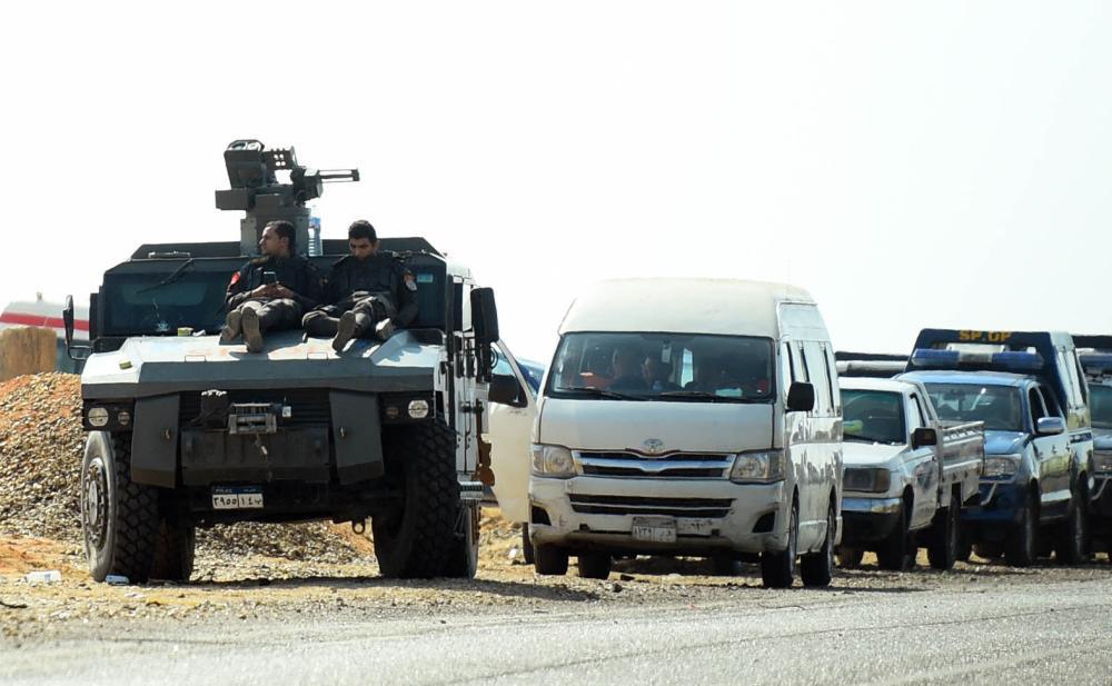 قوات أمن مصرية وناقلات جنود مدرعة على الطريق الصحراوي باتجاه الواحات البحرية قرب موقع الهجوم الإرهابي أمس. (أ.ف.ب)