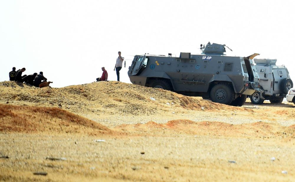 A picture taken on October 21, 2017 shows an Egyptian security forces' armoured personnel carrier (APC) parked on the desert road towards the Bahariya oasis in Egypt's Western desert, about 135 kilometres (83 miles) southwest of Giza, near the site of an attack that left dozens of police officers killed in an ambush by Islamist fighters. An official statement said a number of the attackers were killed, but did not give any figures for losses on either side. Medics and security sources gave a death toll of 35 among police. / AFP / MOHAMED EL-SHAHED