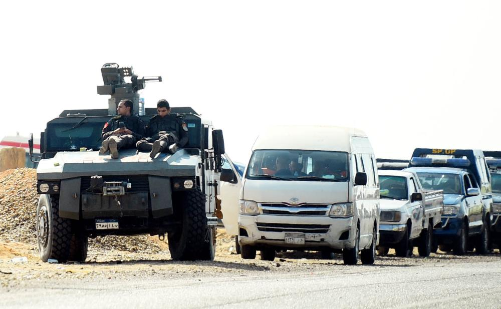 A picture taken on October 21, 2017 shows Egyptian security forces' vehicles and armoured personnel carriers (APCs) parked on the desert road towards the Bahariya oasis in Egypt's Western desert, about 135 kilometres (83 miles) southwest of Giza, near the site of an attack that left dozens of police officers killed in an ambush by Islamist fighters. An official statement said a number of the attackers were killed, but did not give any figures for losses on either side. Medics and security sources gave a death toll of 35 among police. / AFP / MOHAMED EL-SHAHED