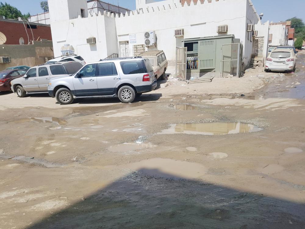 مياه المجاري تنتشر حول المسجد ويبدو مولد الكهرباء المكشوف. (عكاظ)