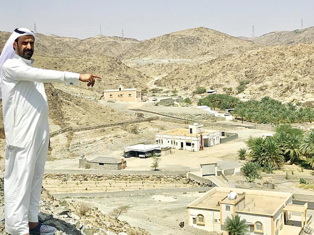بداح الحارثي يشير إلى قرية قوقا من قمة جبل مجاور.   (عكاظ)