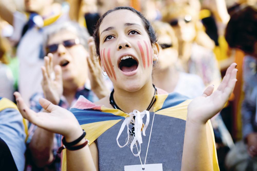 فتاة كتالونية تعرب عن فرحتها بإعلان البرلمان الكتالوني الانفصال عن إسبانيا أمس. (أ.ف.ب)