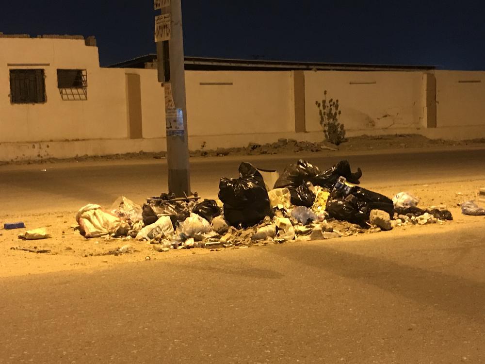 نفايات تنتشر في أحد شوارع الحي.      (تصوير: مديني عسيري)