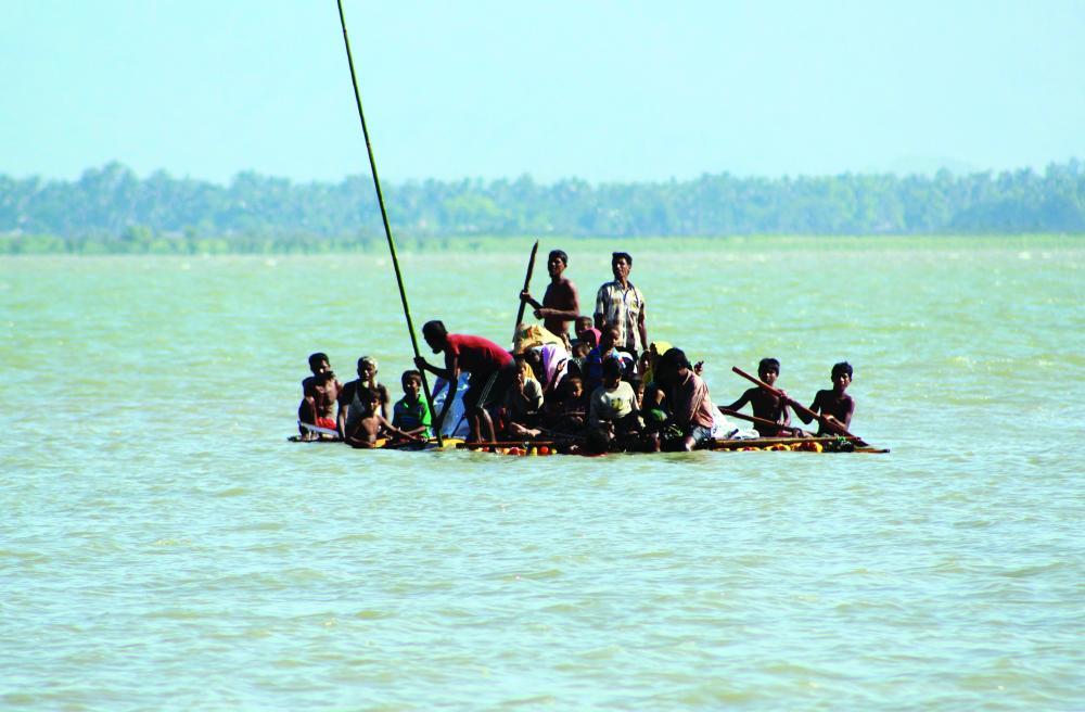 روهينغيون على متن مركب بدائي تعصف به الأمواج، أثناء هروبهم من بورما إلى بنغلاديش أمس.  (أف ب)