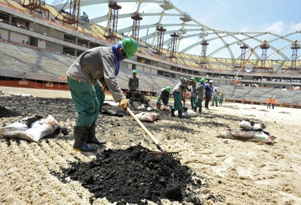 عمال يباشرون أعمالهم في أحد الملاعب بقطر