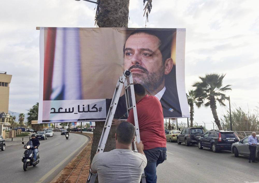 عمال لبنانيون يعلقون ملصقا كبيرا يحمل صورة الحريري وعبارة «كلنا سعد» في أحد شوارع بيروت أمس. (أب)