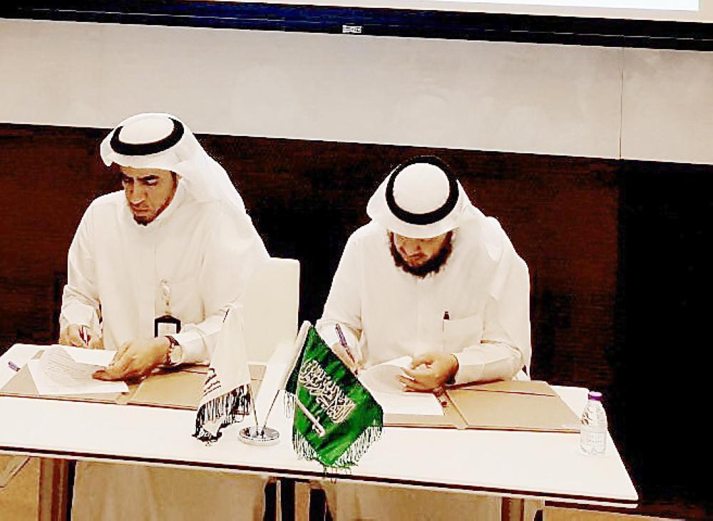 أبوعباة والصبي لحظة توقيع الاتفاقية. (عكاظ)