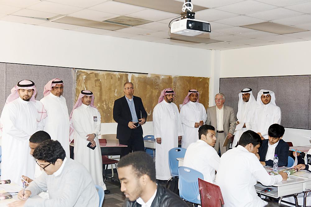 أعضاء الوفد في زيارة لثانوية الملك عبدالله بالدمام. (عكاظ)