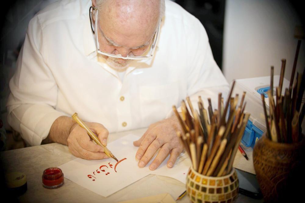 خطاط في المدينة يرسم إحدى لوحاته.