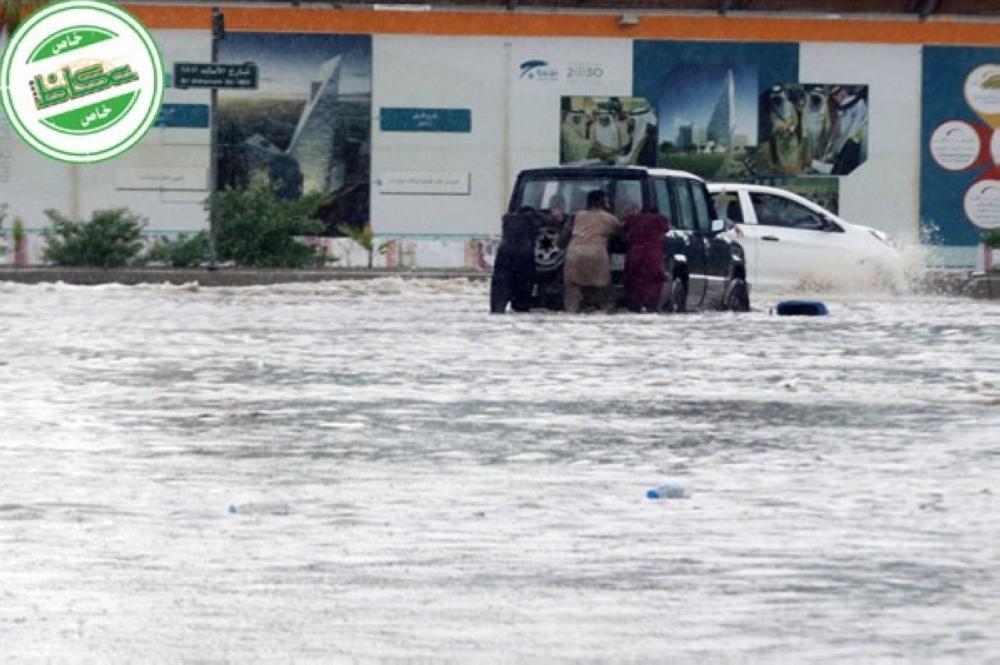 أشخاص يدفعون مركبة تعطلت وسط مياه الأمطار المتجمعة في أحد شوارع جدة