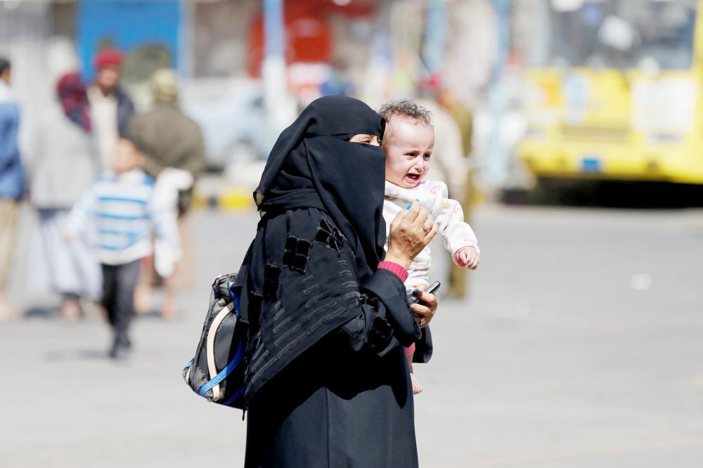يمنية تحمل طفلها في ميدان التحرير بصنعاء أمس. (رويترز)