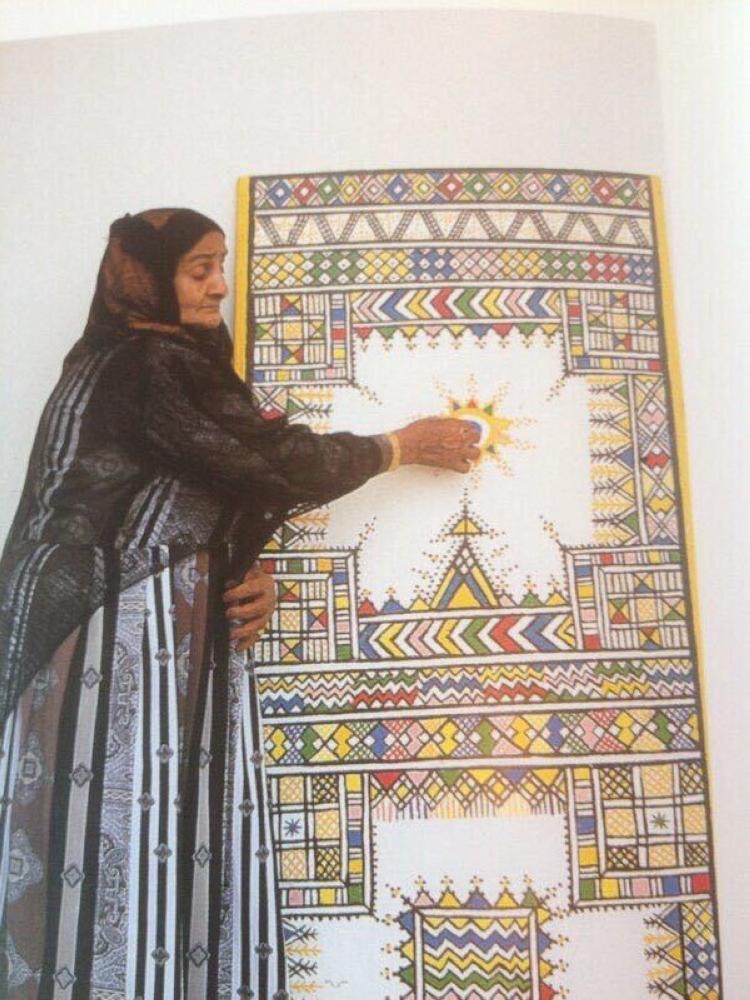 ملهمة الفنانات في عسير فاطمة أبو قاحص -رحمها الله- أمام إحدى لوحاتها لفن القط العسيري.