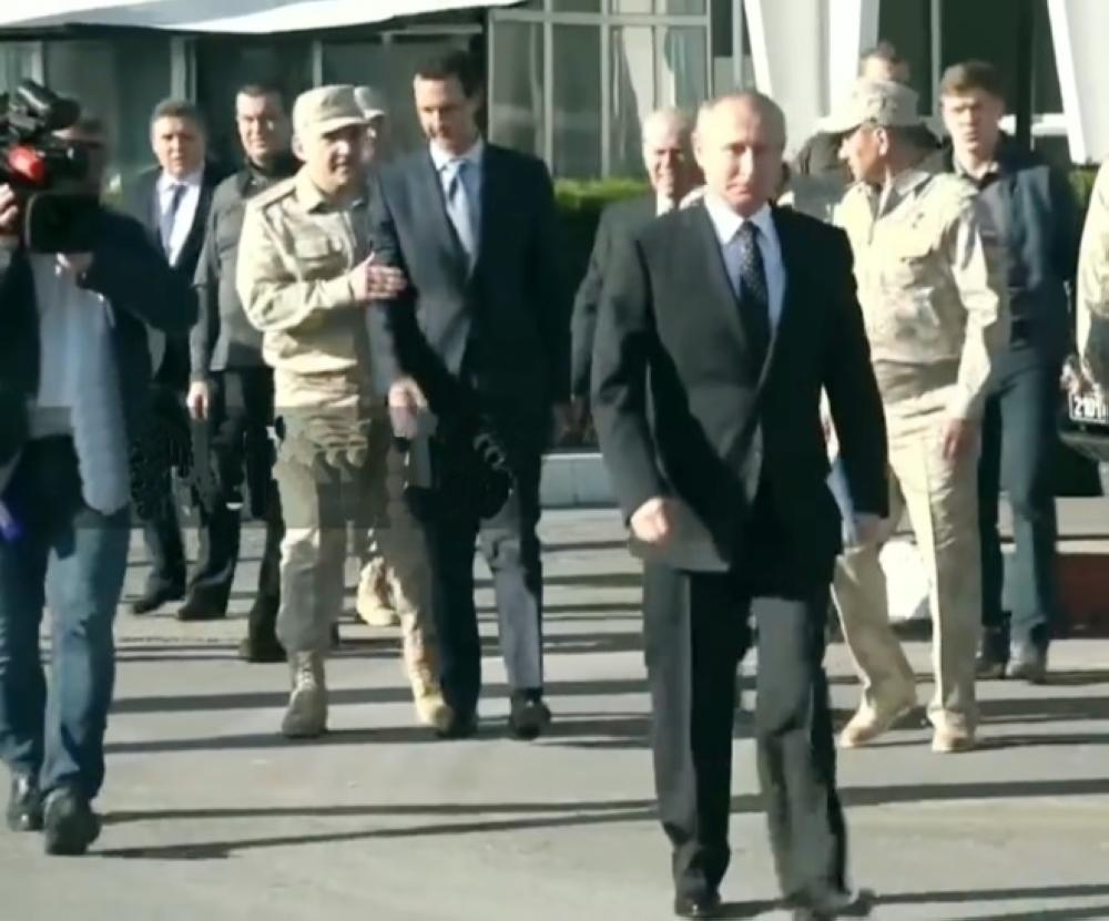ضابط روسي يمنع ـ الاسد الذي بدا مرتبكاـ من مرافقة بوتين أثناء حديثه للجنود الروس في حميميم . (ا.ف.ب)