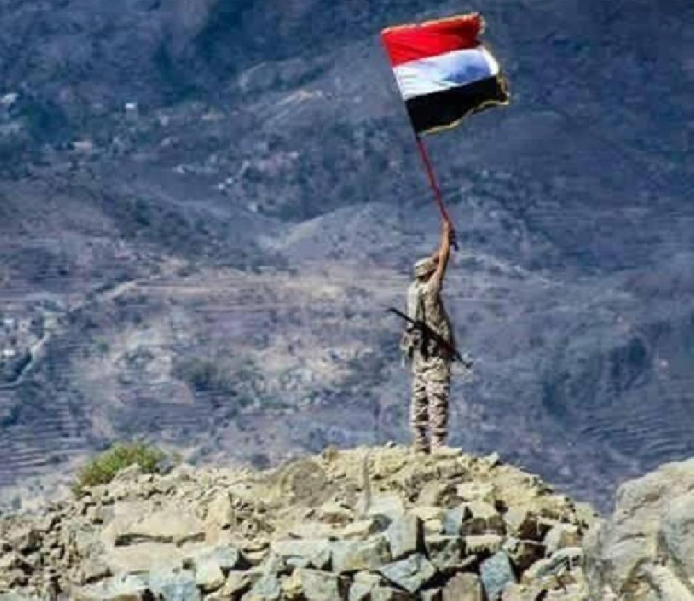 جندي يمني يرفع علم بلاده