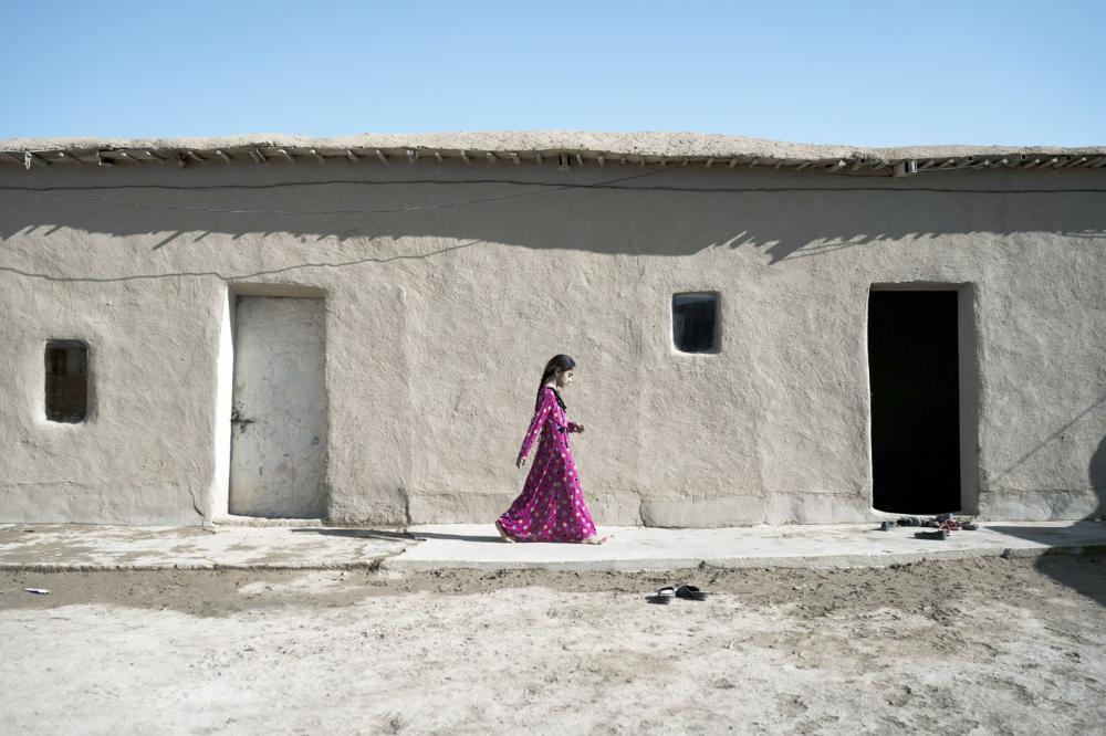 فتاة عراقية تسير خارج منزلها في قرية جنوب الموصل بعد تحريرها من «داعش». (أب)