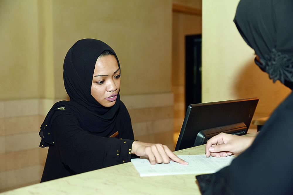 موظفة استقبال في أحد فنادق جدة، أثناء تسجيل بيانات إحدى الزائرات. (تصوير: أمل السريحي)