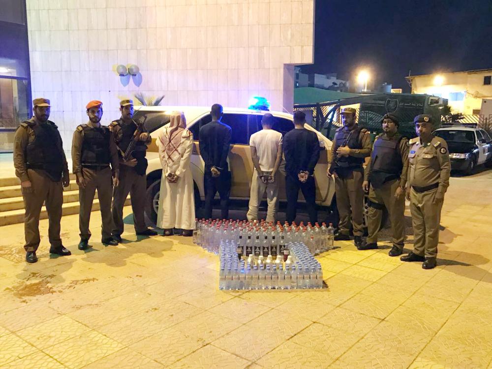 المتهمون الأربعة في قبضة رجال الأمن، وتبدو في الصورة الخمور المضبوطة بحوزتهم. (عكاظ)