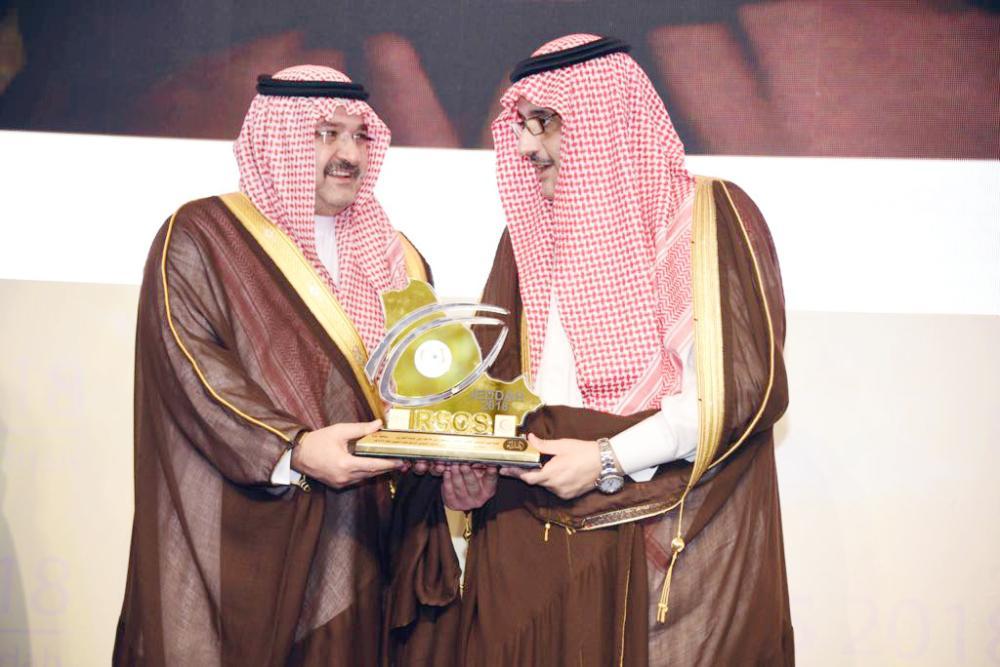 محافظ جدة يتسلم درع تكريم من الأمير عبدالعزيز بن أحمد.