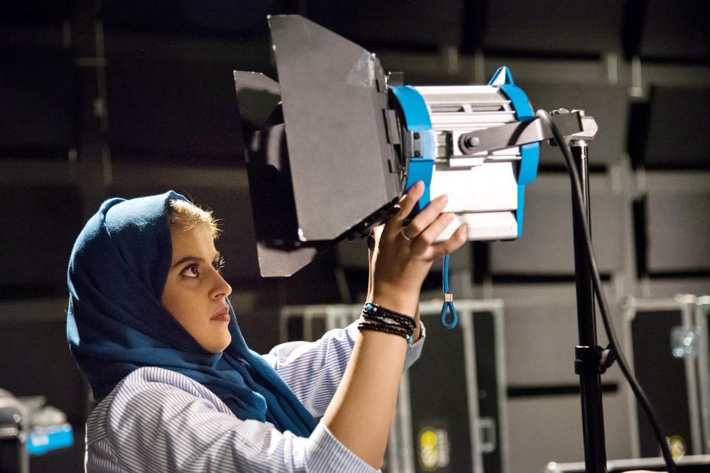 طالبة في قسم الإنتاج المرئي بجامعة عفت أثناء ضبط إضاءة التصوير.