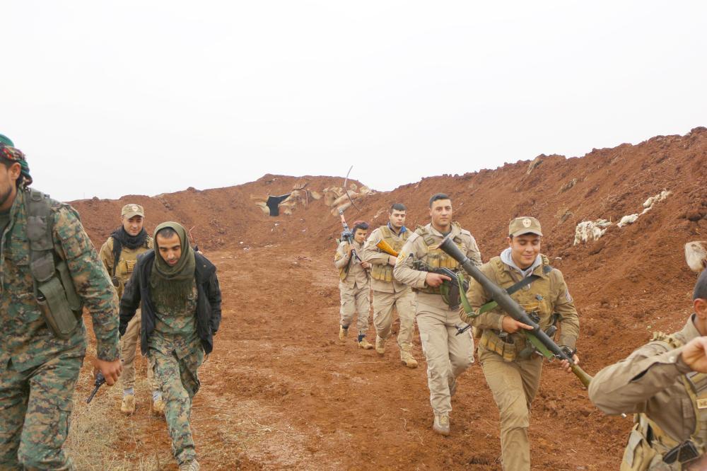 عناصر من قوات (ypg) خلال انتشارهم على إحدى الجبهات. (عكاظ)