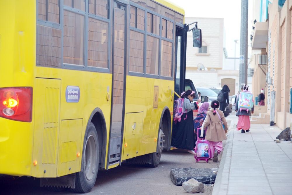 طالبات يغادرن حافلة بعد توصيلهن لمدرستهن بالمدينة صباح أمس. (تصوير: عبدالمجيد الدويني)
