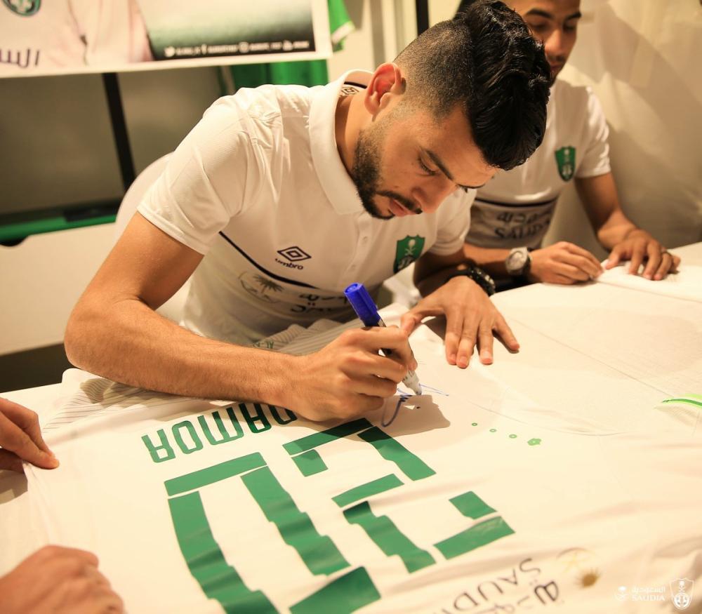 بن عمر أثناء توقيعه على قميص الأهلي.