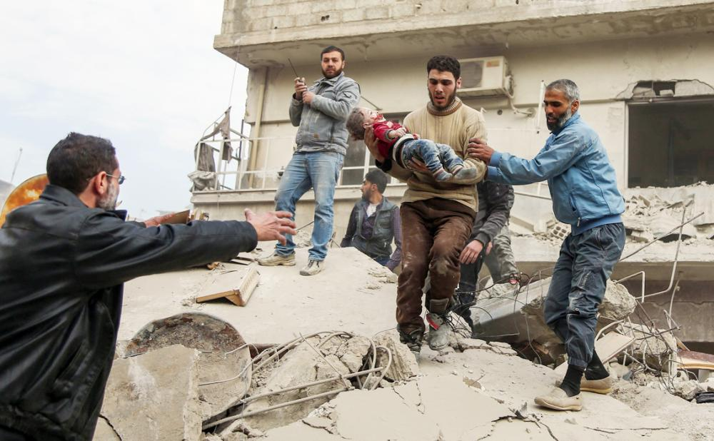 EDITORS NOTE: Graphic content / Syrian men carry a rescued child from beneath the ruins of a building that collapsed following reported Syrian air force strikes in the rebel-held town of Saqba, in the besieged Eastern Ghouta region on the outskirts of the capital Damascus, on February 6, 2018. Fresh regime strikes on a besieged rebel-held enclave near Damascus killed more than 60 civilians on February 6, despite mounting Western pressure on Syrian President Bashar al-Assad. / AFP / ABDULMONAM EASSA