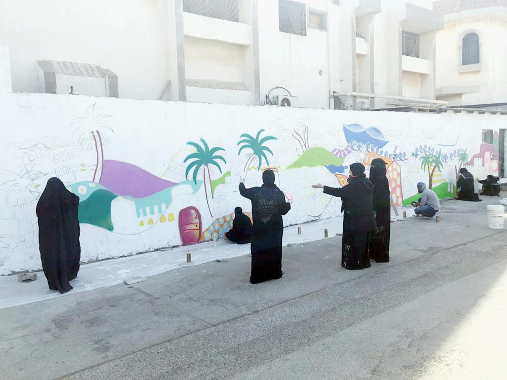 فنانات يرسمن على حائط في صفوى. (عكاظ)