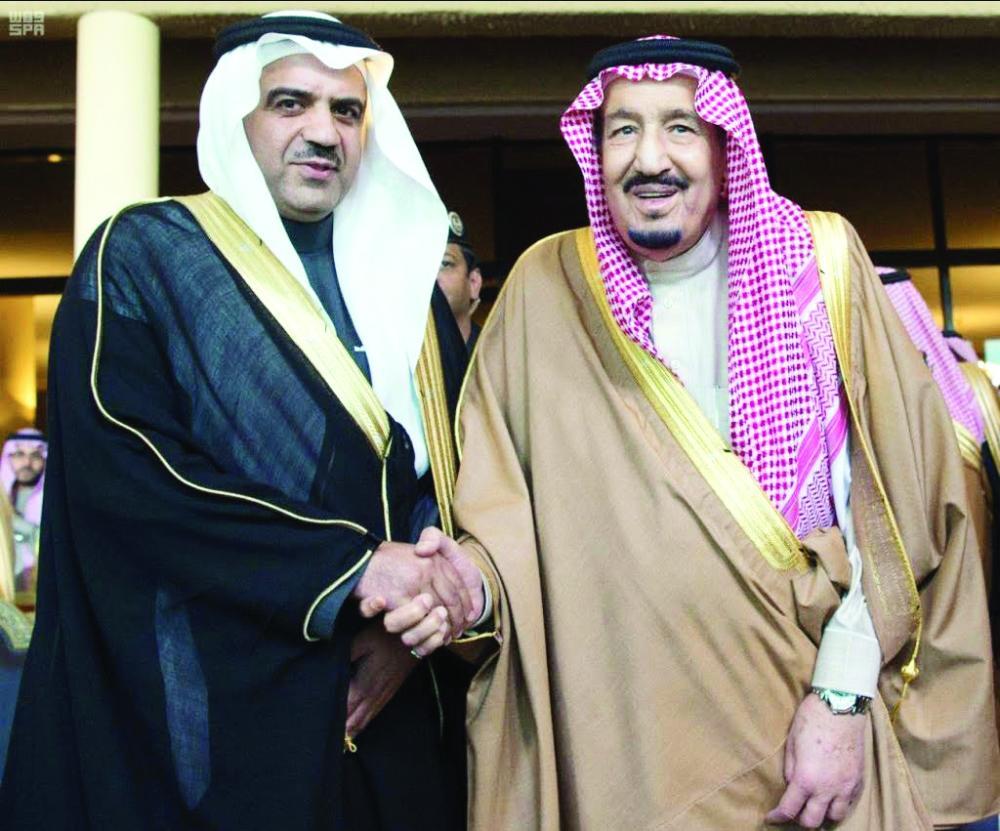الملك سلمان مصافحا الزميل عبدالله الحسون.  (واس)