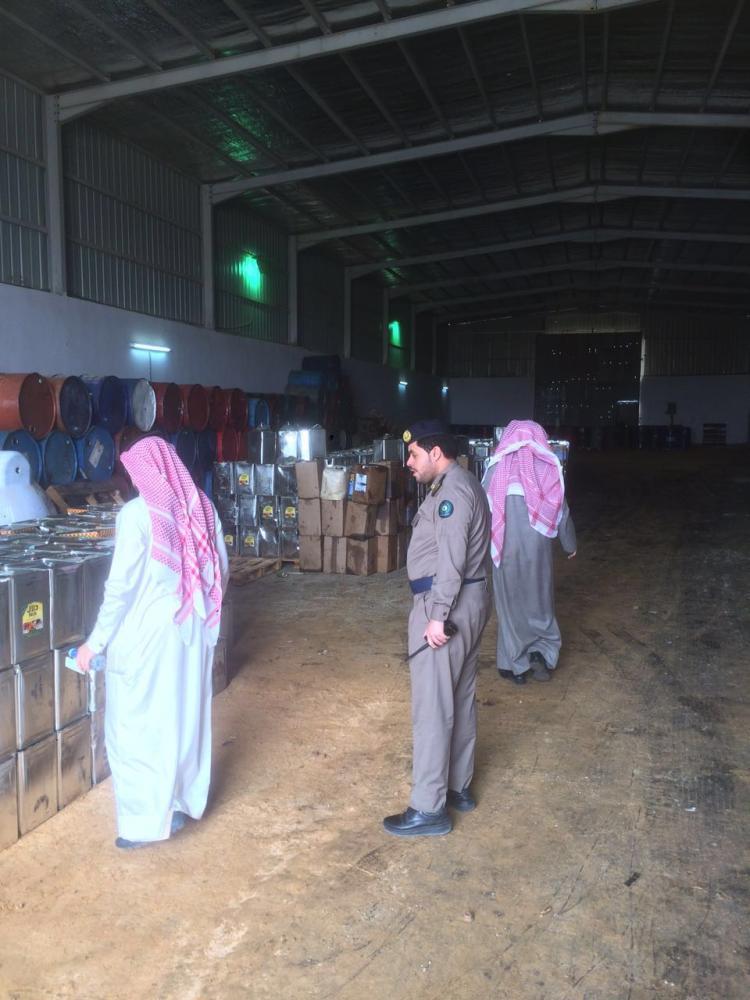 اللجنة الميدانية أثناء ضبطها المواد الموجودة في المستودع المخالف. (عكاظ)