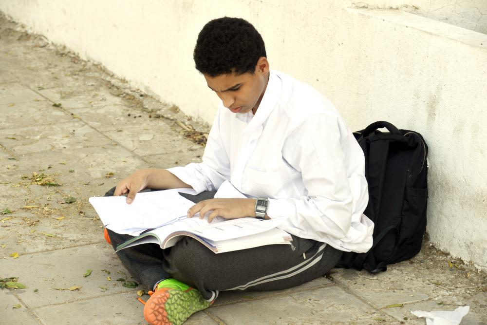 طالب ينتظر والده أمام بوابة مدرسته. (تصوير: أحمد المقدام)
