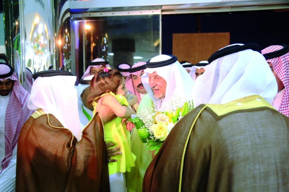 الفيصل يلاطف طفلة خلال افتتاح مكتب العمل بالقنفذة. (عكاظ)