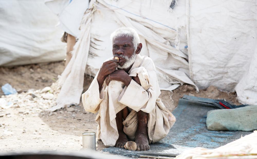 مسن يأكل كسرة خبز خارج خيمة بدائية في مخيم للاجئين في الحديدة أمس الأول جراء التجويع الذي فرضته الميليشيات على الشعب اليمني. (أ ف ب)