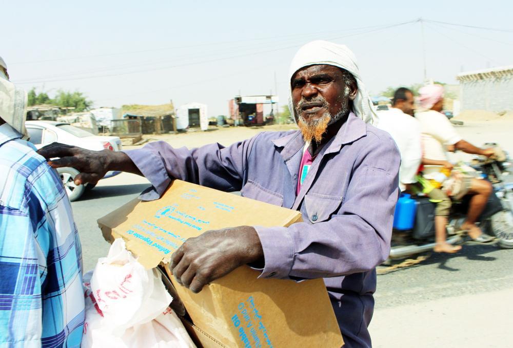 مسن يمني يتسلم معونات إغاثية من إحدى المنظمات الدولية. (أ.ف.ب)
