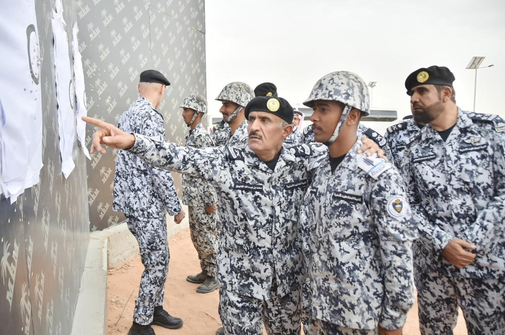 مدير عام كلية الملك فهد الأمنية اللواء سعد الخليوي يشرح لأحد ضباط المستقبل عن الرماية. (عكاظ)
