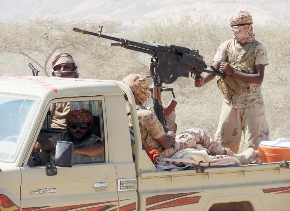 جنود من قوات الشرعية يمشطون جزءا من وادي المسيني أمس الأول. (أ ف ب)