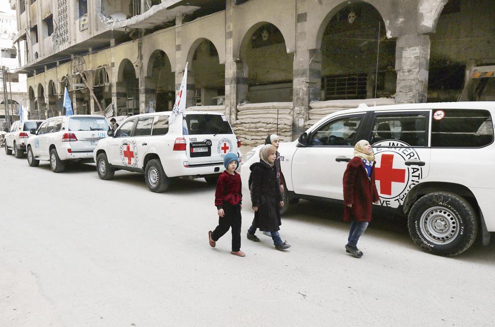 سيارات الأمم المتحدة تسلم مساعدات إنسانية في دوما، وفي الإطار وبالتزامن طائرة للنظام تفرغ حمولتها من القنابل على المدينة أمس. (أ ف ب)