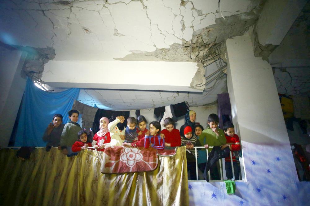 أطفال سوريون يحتمون في أحد الملاجئ تحت أحد الأبنية في الغوطة الشرقية بعد قصف عنيف تتعرض له المنطقة من قبل نظام الأسد. (أ ف ب)