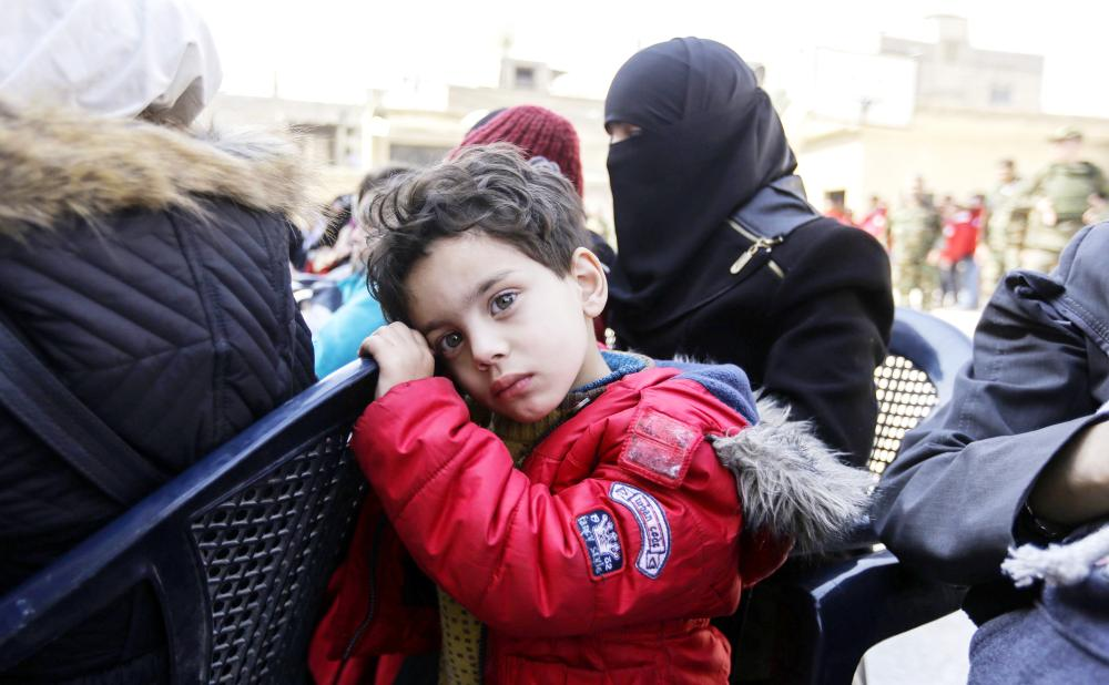 طفل سوري نازح مع أسرته عن الغوطة ضمن المدنيين الذين أجلوا عن المنطقة أمس. (أ ف ب)