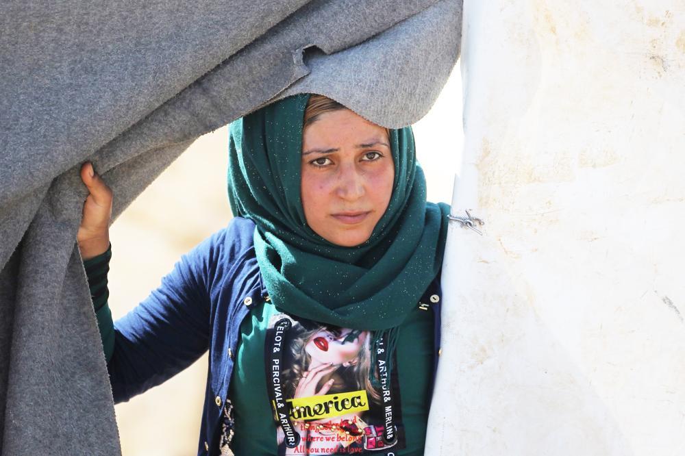 عراقية تطل من خيمتها في مخيم للنازحين في تكريت أمس. (أ ف ب)