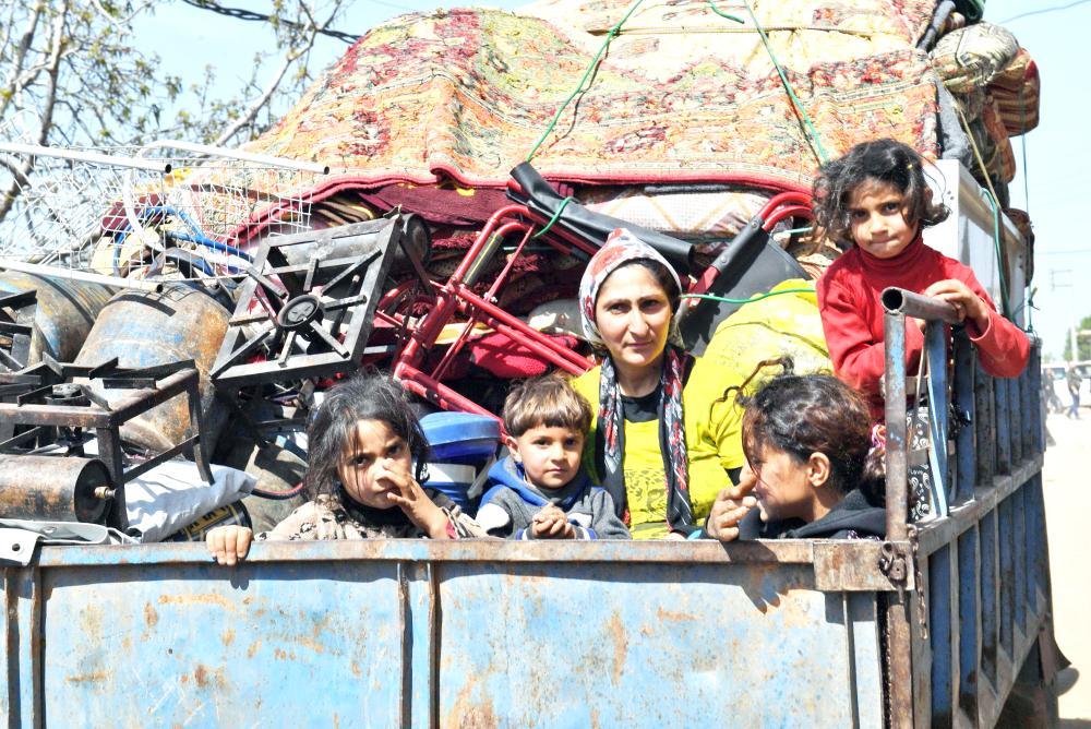 سورية كردية وأطفالها يستقلون سيارة خلال نزوحهم من عفرين عقب اقتحام القوات التركية لها أمس. (أ.ف.ب)