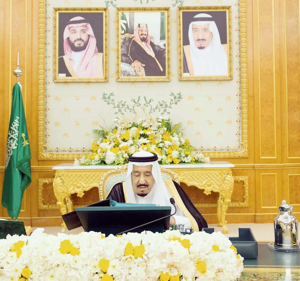 الملك سلمان مطلعا على بعض الأوراق خلال رئاسته جلسة مجلس الوزراء. (واس)