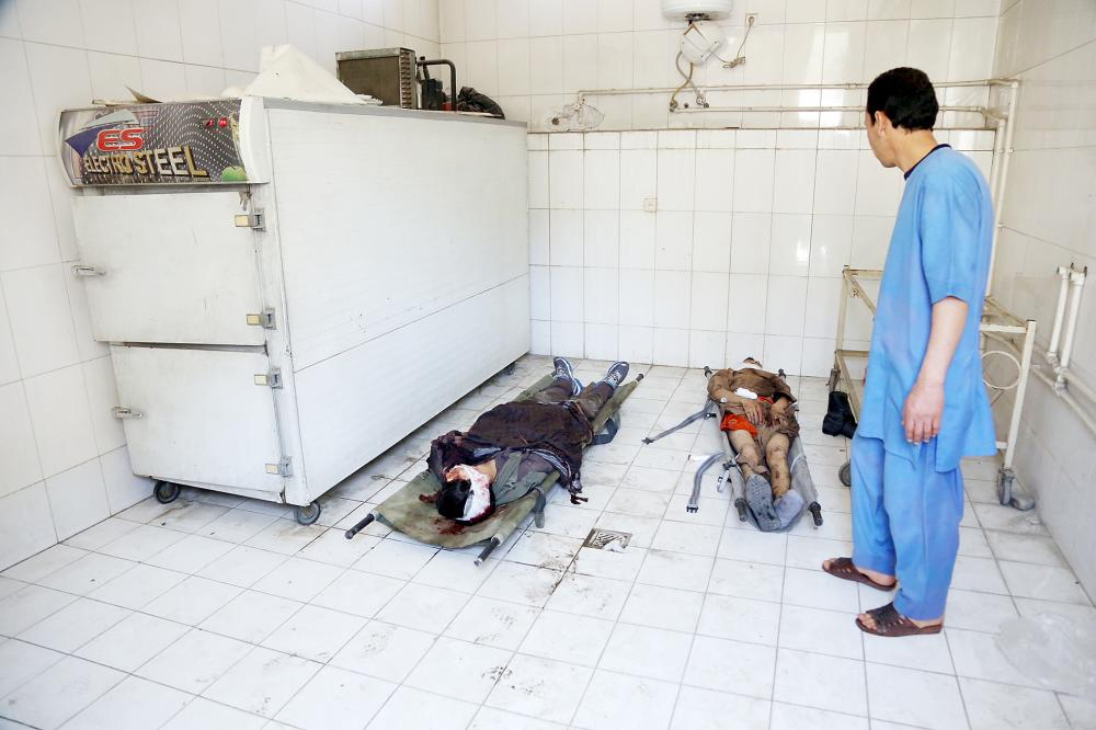 جثتا مدنيين قتلا في الهجوم الانتحاري أمام جامعة كابول أمس. (أ ب)