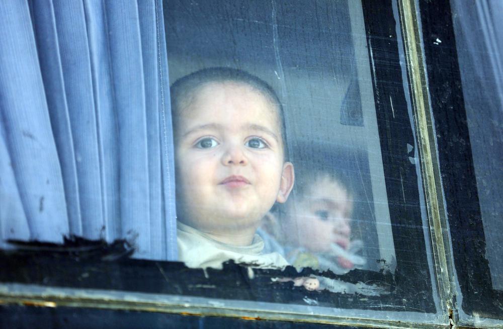 طفل سوري يطل من نافذة حافلة تقل عدداً من مسلحي المعارضة وأسرهم لدى مغادرتهم الغوطة أمس. (أ ف ب)