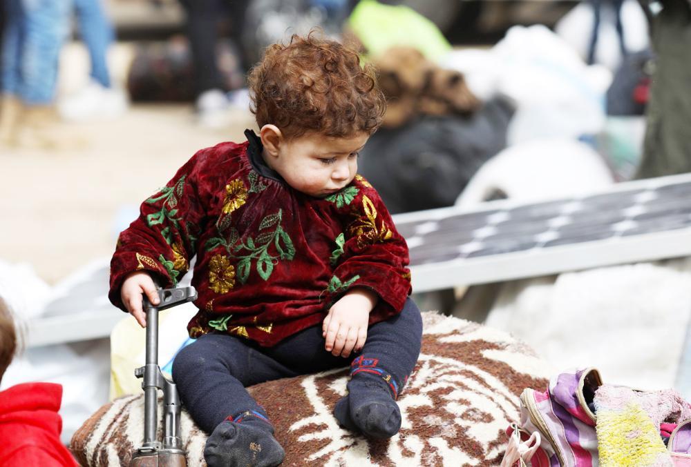 طفل سوري يجلس على حقيبة ممسكا فوهة بندقية بعد وصول حافلة نازحين من الغوطة إلى حماة أمس. (أ ف ب)